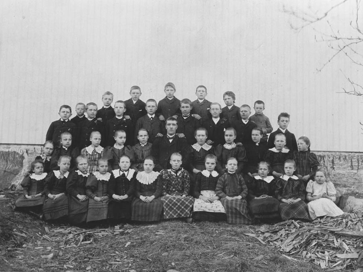 Lærer Tho med sine elever bak Gjedsjø skole.