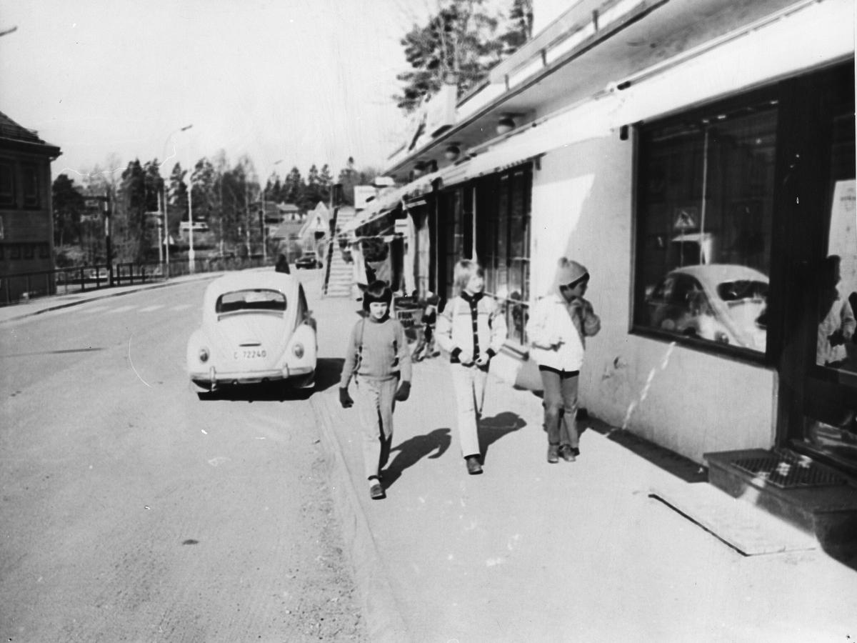 Kolbotnveien med Kolbotn stasjon så vidt synlig til venstre, og apotekergården til høyre.