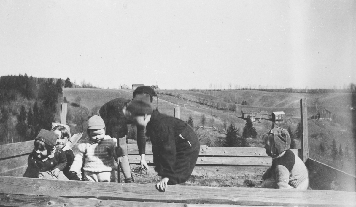 Barn i sandkassa.  Søstua, Grini og Nessletta oppe på sletta.