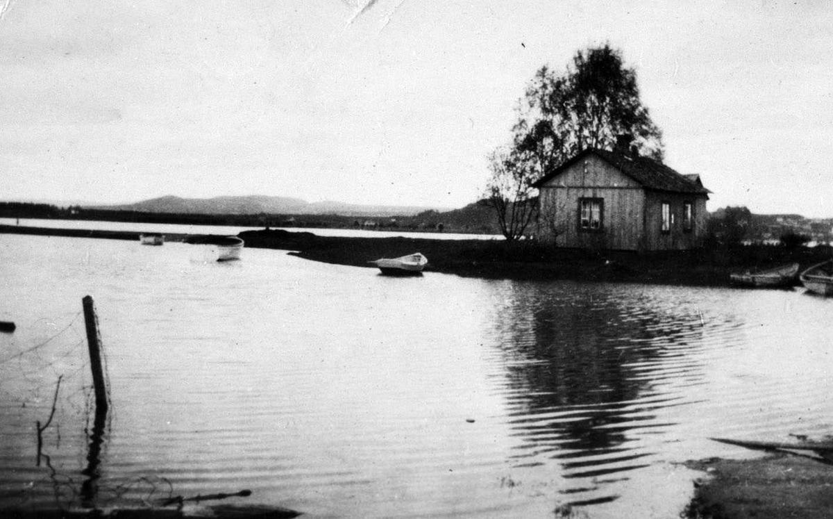 Lillestrøm Volla Flom? Et hus på en odde med vann på to sider. Flere robåter.