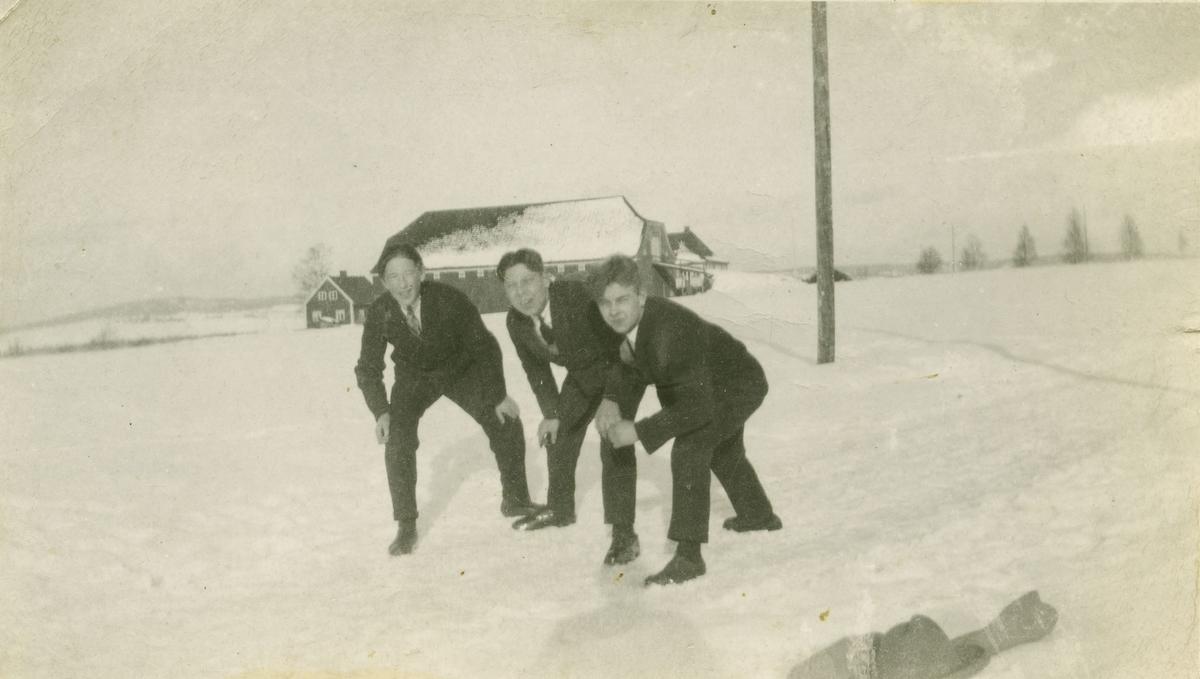 Tre yngre menn i dress i sneen. Stalsberg gård i bakgrunnen.