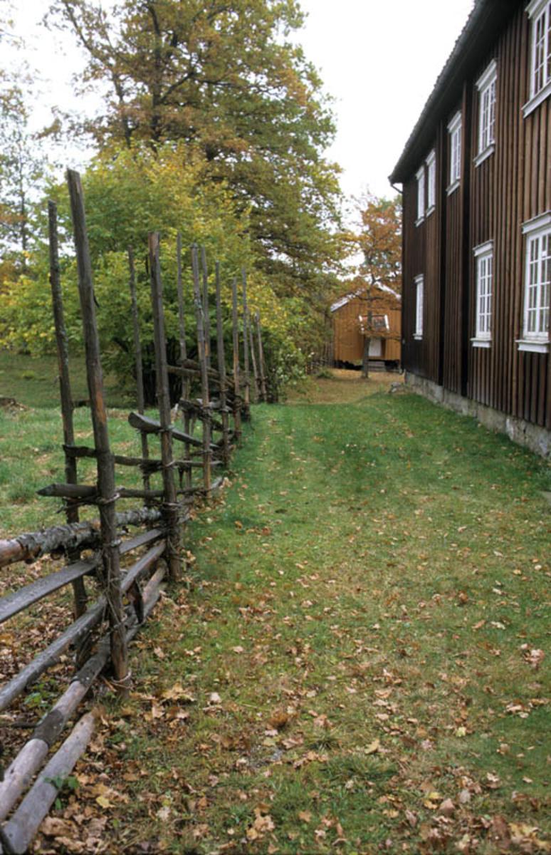 Follo museum: Børsumbygningen, stakitt, gress imellom hus og stakitt.