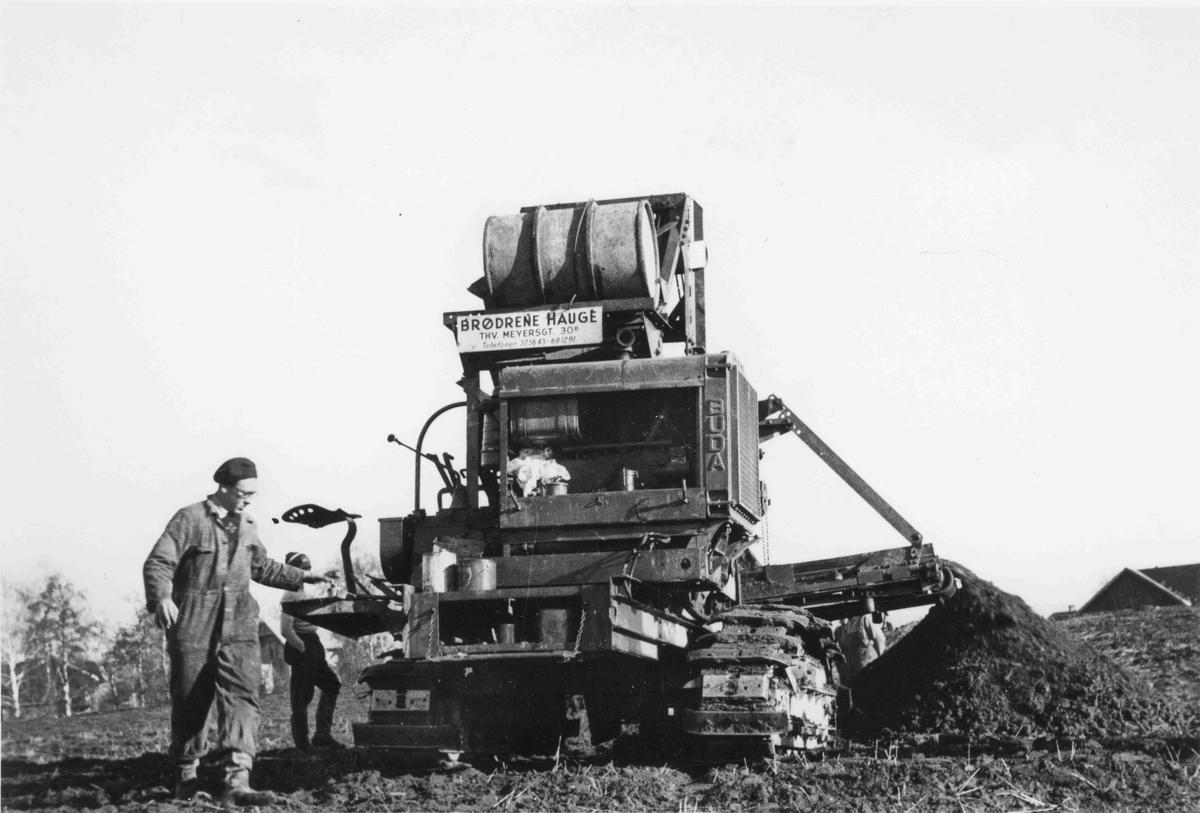 Maskin som graver grøft til vannledning, rett bak Nebbenes. Firma: Brødrene Hauge, Thv. Meyersgt. 30, Oslo.