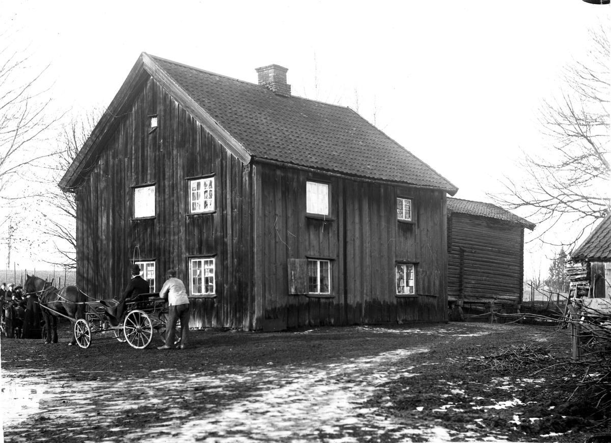 Hest og vogn utenfor eldre hus.