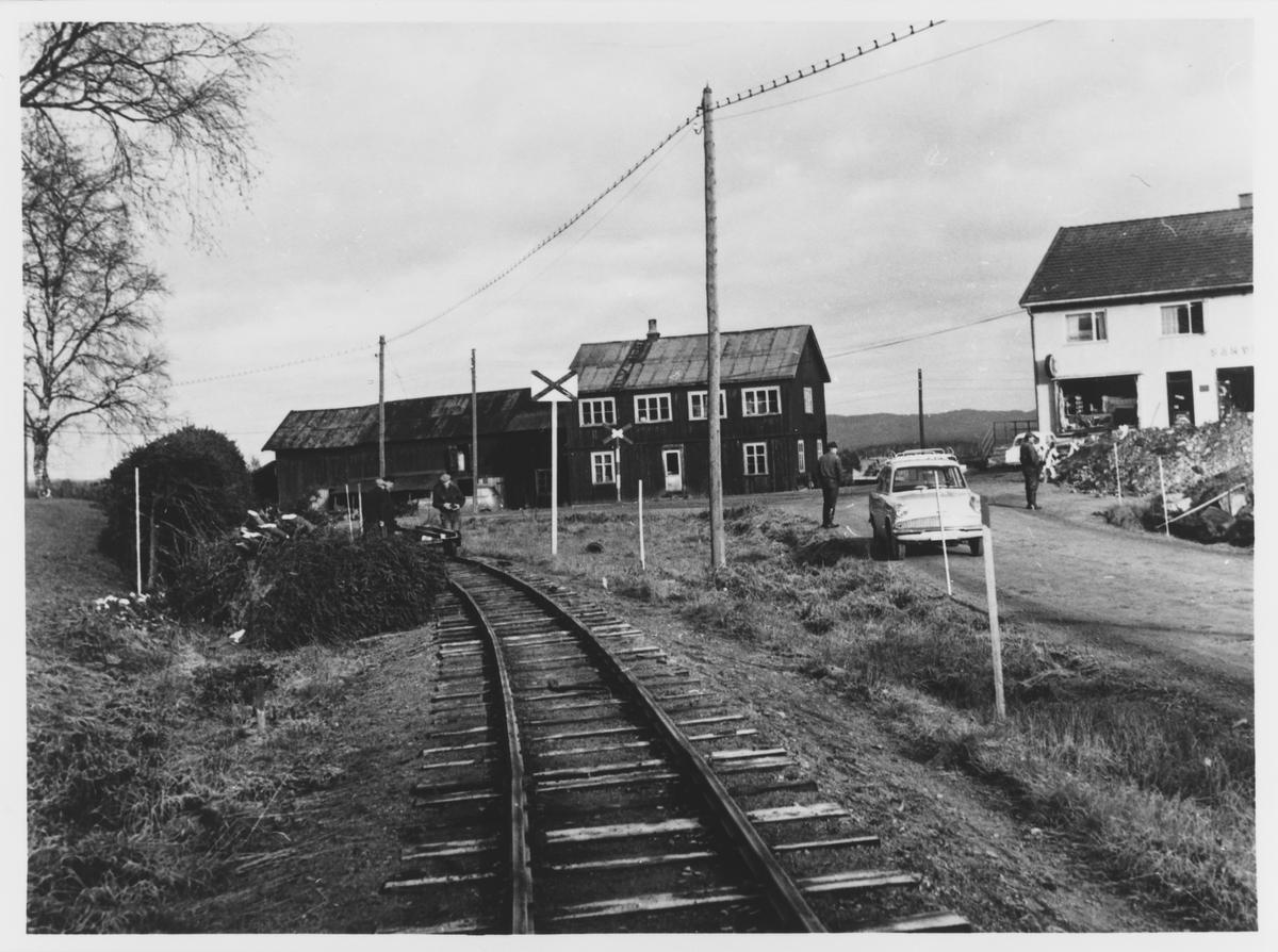 Riving av Urskog-Hølandsbanens spor på Bjørkelangen. Arbeidet utføres med håndkraft, og skinnemateriellet kjøres inn med håndtralle.