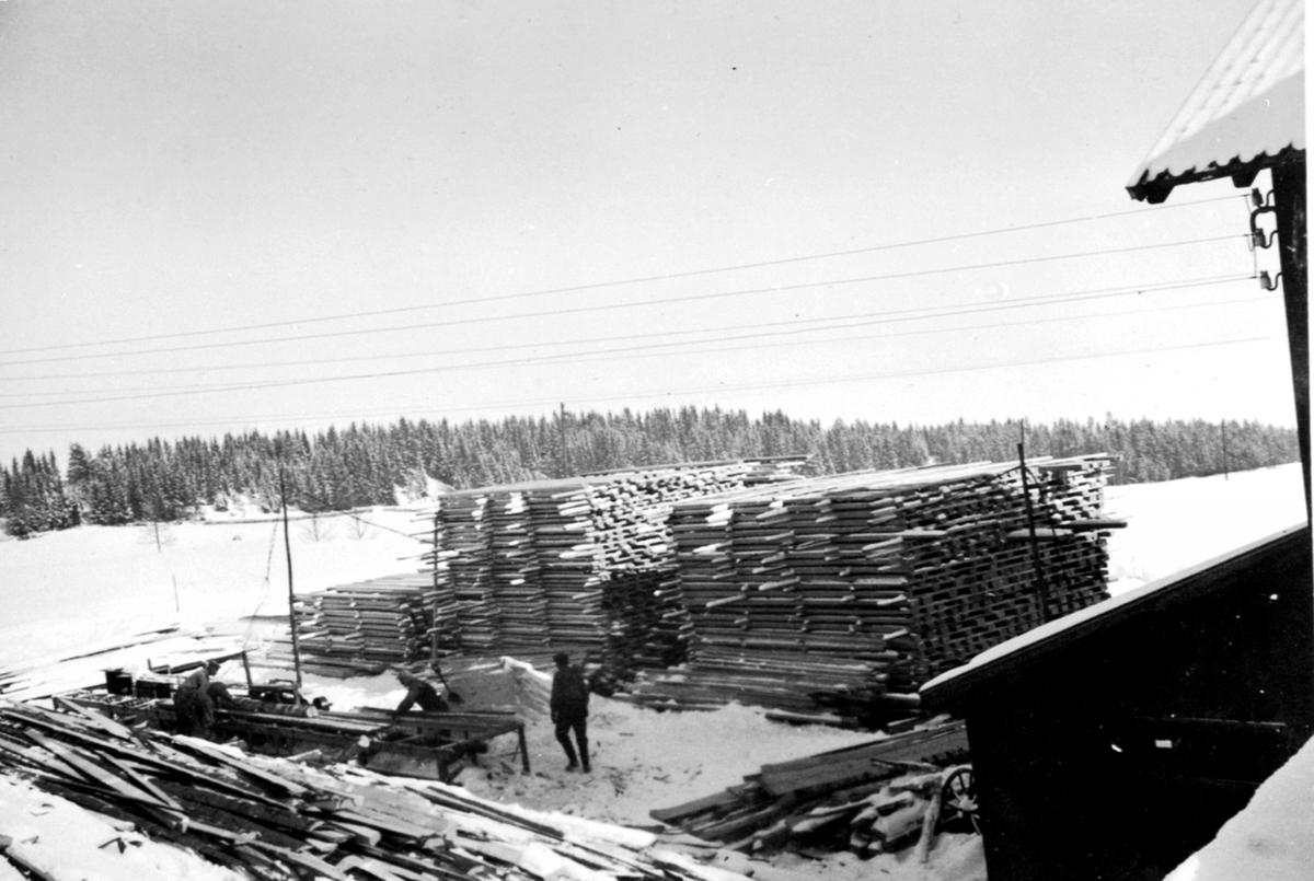 Skjæring av tømmer til materialer. Planker lagt opp for tørking. Sagbruk på Lodviken, Helgøya. 3 menn jobber.