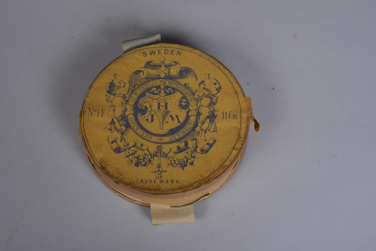 Rund gul eske av papp med pålimte runde papirlapper på bunn og på lokk med informasjon. Lappen på bunnen har produsentens logo. Esken inneholder runde filterpapir for bruk i laboratorium. Lokket kan tas helt av.
