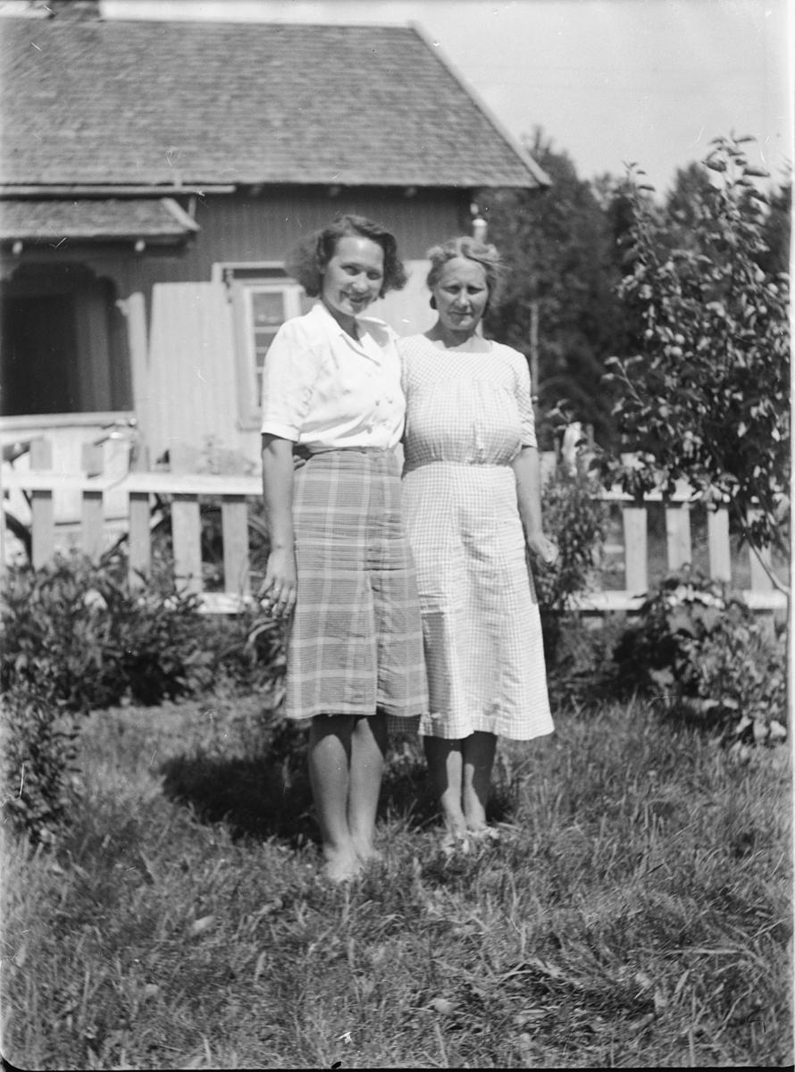 To kvinner i en hage med gjerde.
