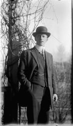 Baker Johs. Johannessen jr. i skalk, hatt, dress.