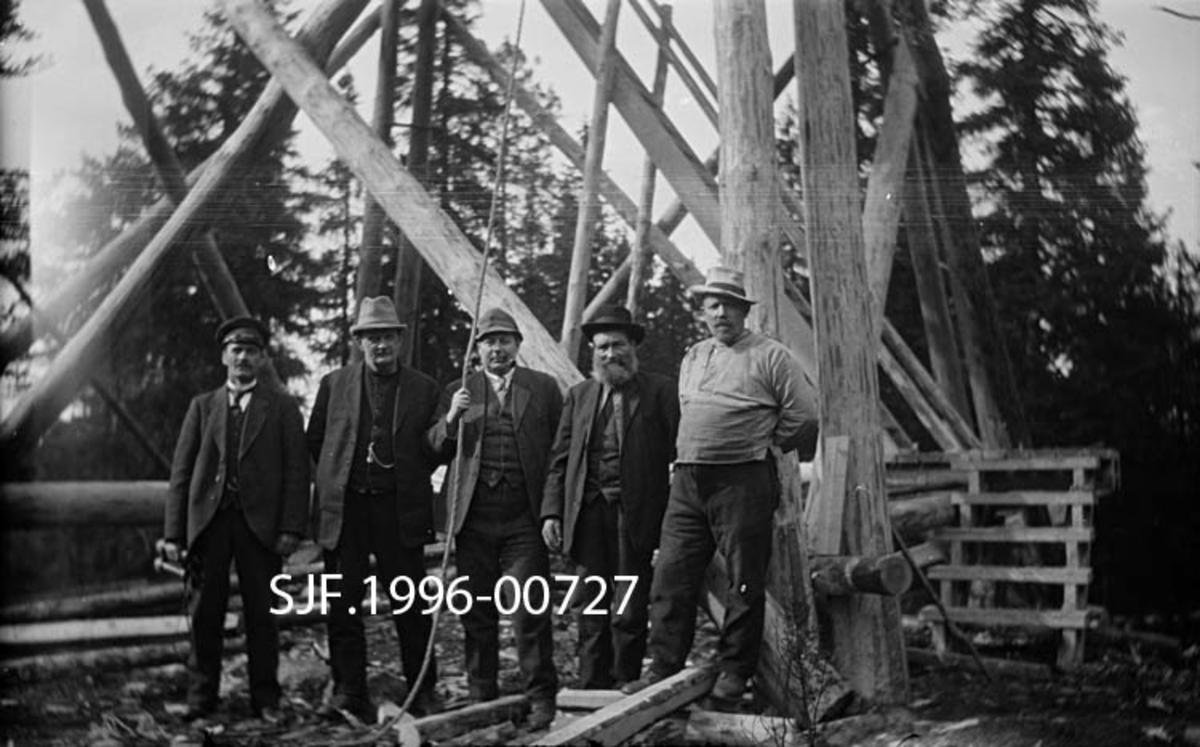 Fra tårnbygginga på Lundbergseteter skogbrannvaktstasjon i 1936.  Fotografiet viser fem menn som står på rekke ved foten av en tårnkonstruksjon, som etter det nybarkete stolpetømmeret og materialrestene på bakken å dømme var under oppførelse.  Karene er ulikt kledd, noe som antyder ulike roller.  Mannen til høyre er arbeidskledd, med vadmelsbukse, busserull og en litt røff hatt.  De fire andre har dresser og vester med klokkekjeder.  En av dem har til og med spaserstokk.  Det er rimelig å tenke seg at dette er representanter for byggherren, som er på befaring.  Mannen helt til venstre er også fint kledd, men har skjermlue, som ofte ble brukt av sjåfører.