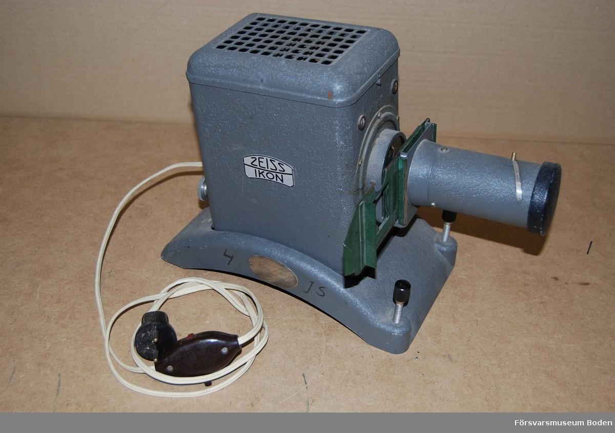 """Med hållare för diabilder monterade i ramar med yttermåtten 5 x 5 cm. För 220 volt, strömbrytare monterad på sladden. Objektiv av typen Ikon Orikar, 10 cm. Silverplakett monterad på sidan av projektorns fot med texten """"Gåva av Riksförbundet för Sveriges Försvar. Plaketten har kontrollstämpeln O 8, vilket daterar den till 1940."""