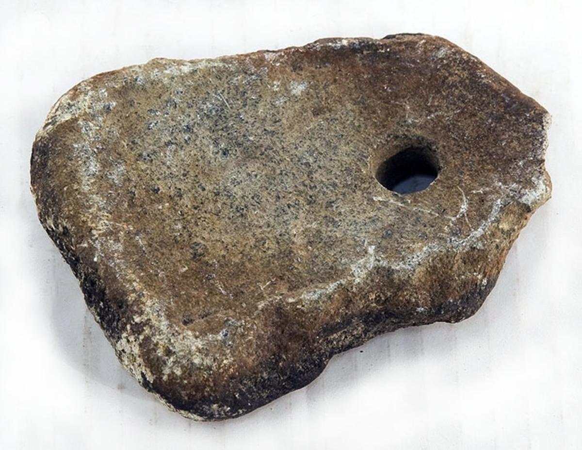 Flat stein med rundt hull den ene enden. Litt tilhugget. Til forankring av små, flytende gjenstander.