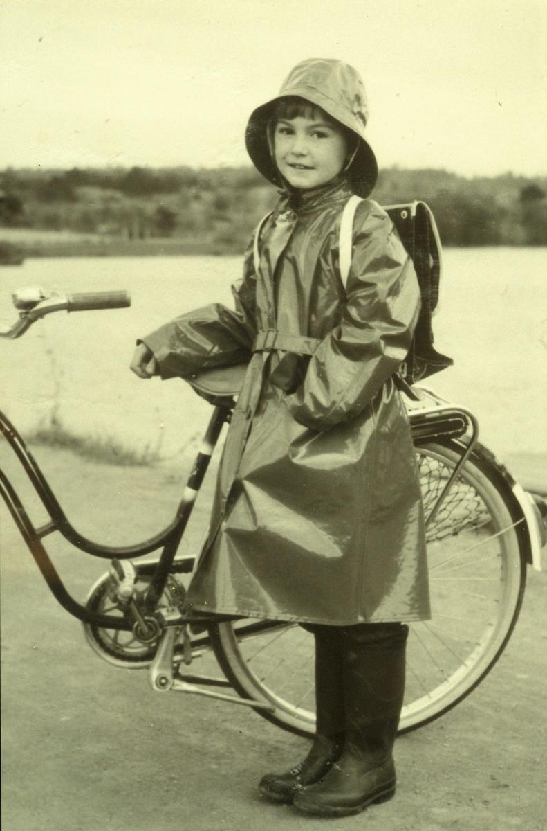 Reklame, jente i regntøy med sykkel og ransel på ryggen, uten tekst