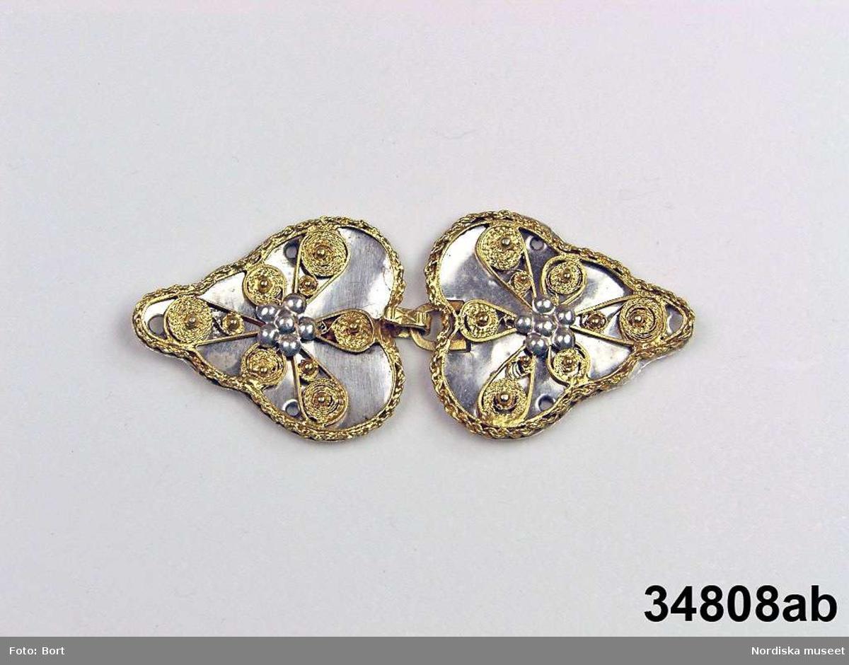 """Huvudliggaren (år 1882-1883): """"34.808 A-B Ett par spännen trol. fr. Skåne. G. ss. 34,805 [= G. af artisten A. Montan i Düsseldorf 28/2 1883].""""  a-b) Spänne, bestående av två hjärtformiga silverplattor med vågig, profilerad kontur. Pålött, förgyllt  filigranornament. På varje spännhalva mittdekor i form av fembladig blomma (troligen vitkokad), fäst genom ett hål med flikar på baksidan. Spännet knäppes med hake och hyska (förgyllda). På hakens ovansida ett """"x"""". På baksidan av varje halva otydlig stämpel, möjligen H4, årsbokstav för 1838, slagen ovanpå en annan, oidentifierad stämpel. /Marie Tornehave 2008-09-23"""