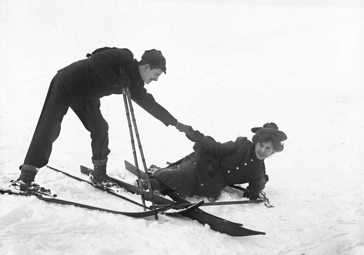 Kvinne og mann på ski i snødekt landskap. Mannen hjelper kvinnen opp etter et fall.