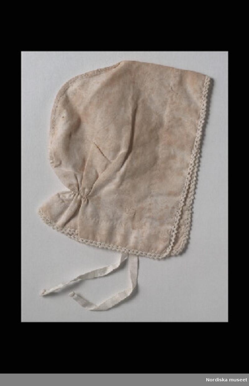 Inventering Sesam 1996-1999: H 13,5 cm Mössa till docka av vitt linne, rynkad i nacken, smal virkad uddspets runt kanten, knytband i bomull. Tillhör docka 202.174 Leif Wallin jan 1997