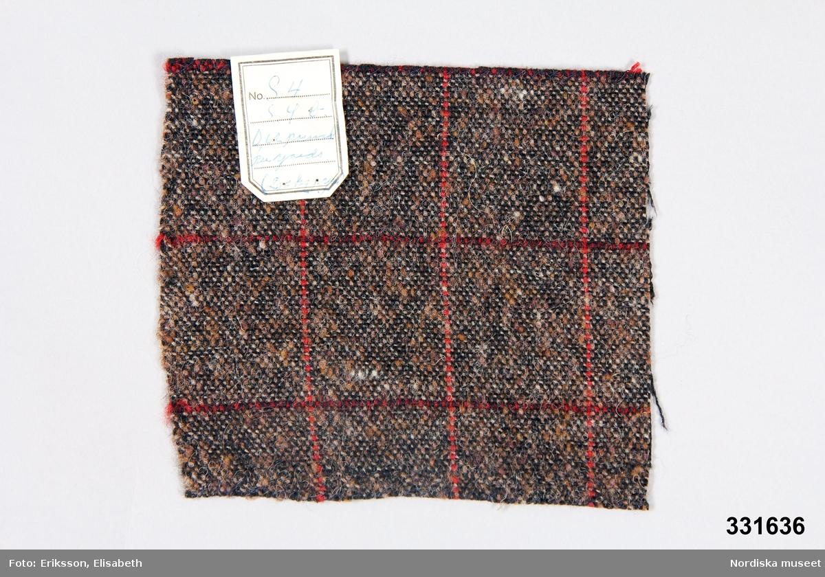 """Tygprov, tuskaft, svart varp, brunt inslag. En röd varptråd, var 5 cm. Rött inslag, dubbeltråd, ca var 6 cm.  Vidfäst pappersetikett: """"No  S 4  S. 4 b  0,62 pound   per yards  (2,8 hg p yar)    280gr/y    Samma  vikt det  brun-svarta""""17x15,5 cm /Magdalena Fick 2011-11-16"""