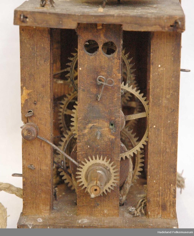 """a) urverk; mangler tannhjul i front, samt tallskive og """"dører"""" i sidene. b-d) klokkelodd"""