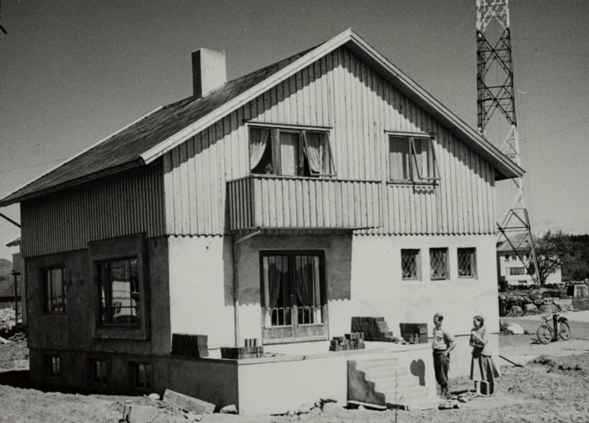 Enebolig, bygget av en selvbygger - Gunnar Nygård med kona foran huset