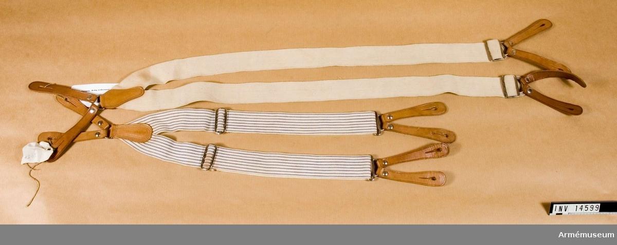"""Grupp C I Bärremmar till tornist, 2 st av tjockt bomullsband khakifärgade (på engelska """"wibbing""""), beslag på ändarna av mässing. På båda banden står: """"M.E.Co."""" (uppåtriktad pil) """"1910"""". Remmarna har två pappersetiketter: 1. En är sammankopplad med en svart klädesbit med rött sigill på vilken finns en stämpel - vapen för """"Royal army ordonance corps"""".  En sköld med tre kanoner och krona, efter Regiment Badges and service caps. London. 1941.  Samhörande nr är AM.14560, 14599"""
