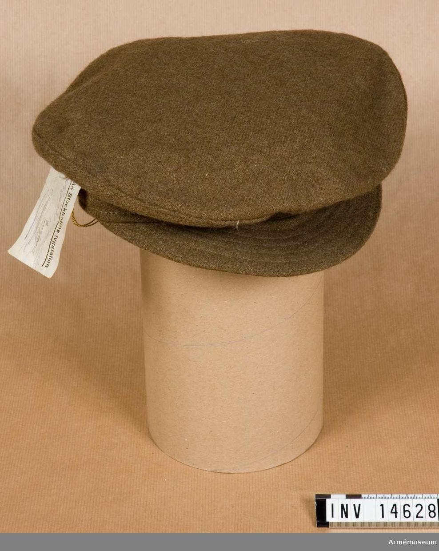 """Grupp C I. Skärmmössa av khakifärgat kläde med 4 cm brett bräm av samma genomsydda kläde med två par lufthål på sidorna. Hakremmar saknas; men på mössans sidor finns två små guldfärgade kappar med engelska statsvapnet. Foder av svart vaxduk med stämpel på vilken det står: """"Gaunt & Hudson L"""" (upphöjt o), """"6 1/2"""", """"1910"""". Skärm av samma kläde - genomsydd."""