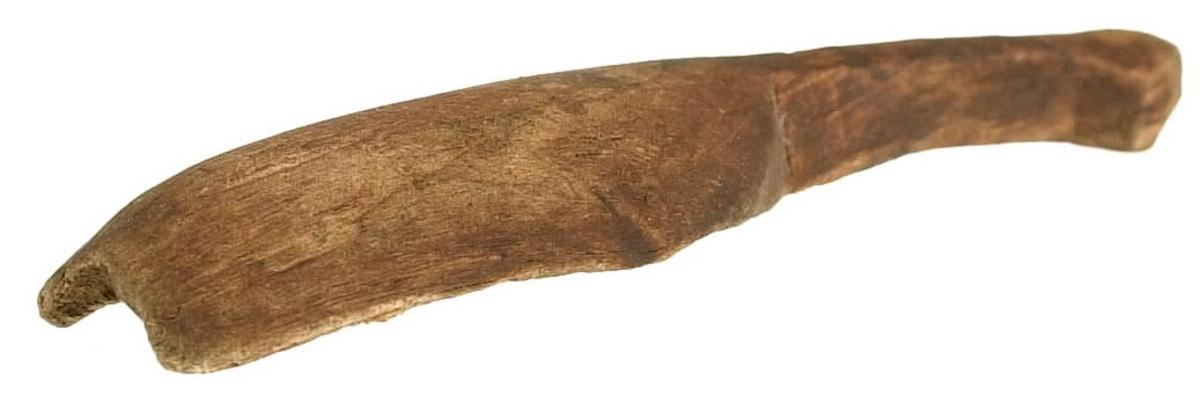"""En träsked. Skedbladet har ursprungligen sannolikt varit ovalt. Skedskaftet är i förhållande till skedbladet kort och smalt. Skaftets ände är profilerad. På skeden syns rödbrun färg, som möjligen är spår efter bemålning. Skeden är i relativt dåligt skick, med sprickor. Skaftet har troligtvis """"vridit"""" sig och fått en sned form. Större delen av skedbladets ytterkanter saknas."""