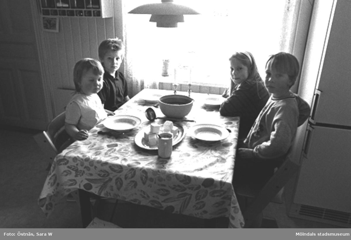 Fyra barn som sitter runt middagsbordet, 1980-tal.