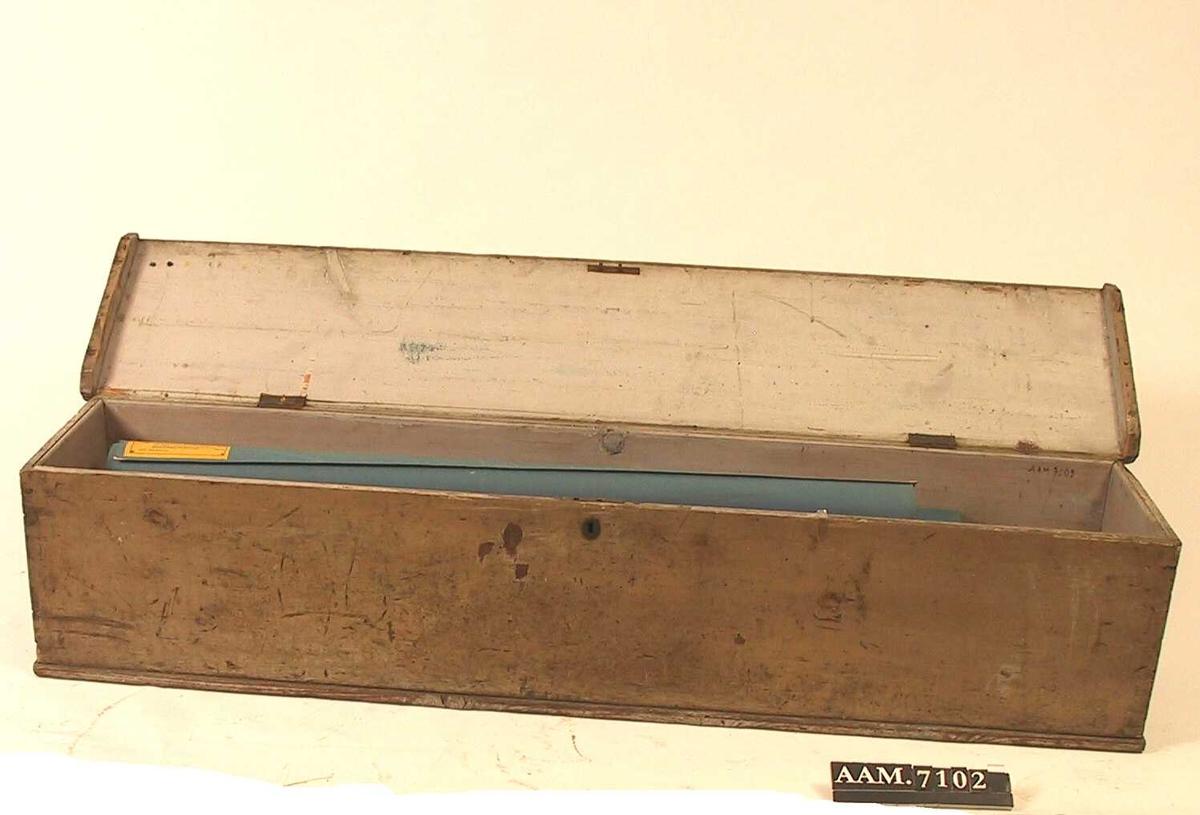 Lang, smal  kiste med flatt lokk, ovalt lite nøkkelskilt pm. Malt blågrønn utv.  Innvendig et tynt og uregelmessig strøk  maling, i lokket gullig. En blågrønn lerrets,rop  i den ene side.  Tilstand mars 1967: flekket og oppskrapet, ellers bra.