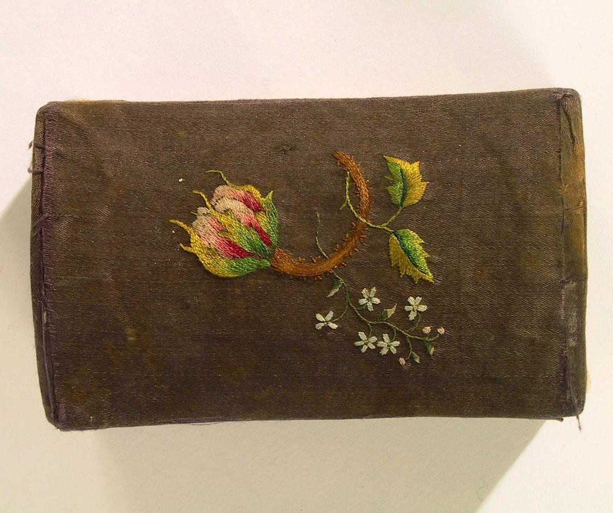 Blomster og blader på lokket. Bølgeformede blomsterranker og sammenknyttet lenke på frem- og baksiden av kisten. På kortsidene to lenker, to paljetter på den ene siden, disse mangler på den andre. Flatene innrammet av smalt bånd.