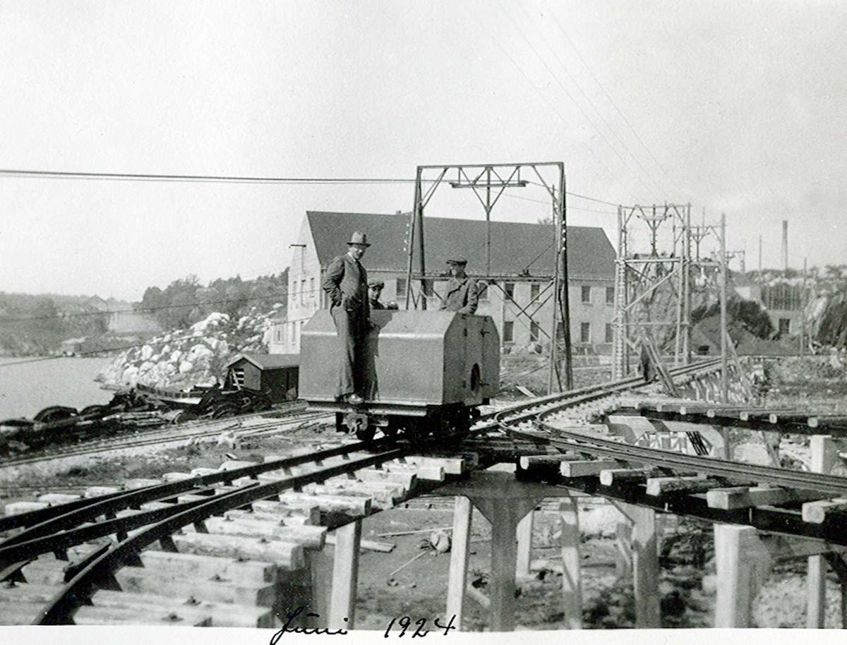 """""""xx/06-1924"""" Nitriden. Skinneanlegg, """"høybanen"""", med bærende konstruksjoner, skinner, sviller og dieseldrevet lokomotiv. I bakgrunnen bygning for verksteder, materiallager og kontorer. Taubanen. Tromøysund til venstre."""