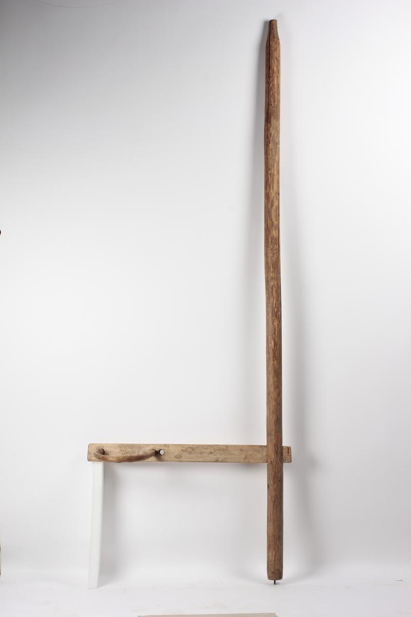 """En stolpe med """"arm"""". En trebøyle er festet på """"armen"""". Stolpen ble festet fra gulv til tak. Barnet ble plassert i trebøylen slik at den kunne gå rundt stolpen."""