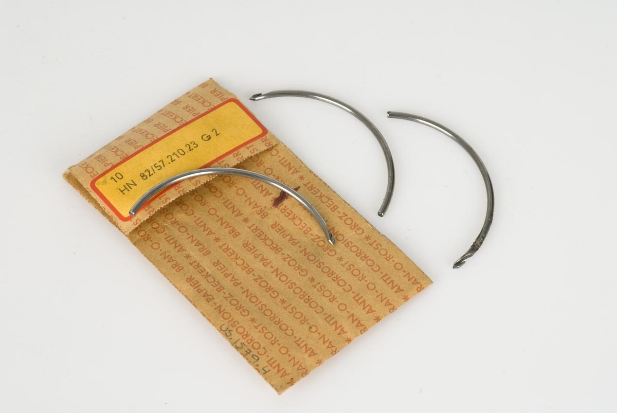 Durknåler av metall  i papirpakning med påskrift. Pakningen har en påklistret gul og rød lapp med stempel.
