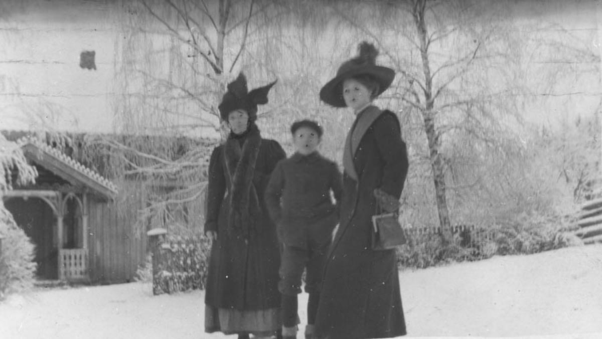 To damer i hatt og kåpe og en gutt i vintersnøen.
