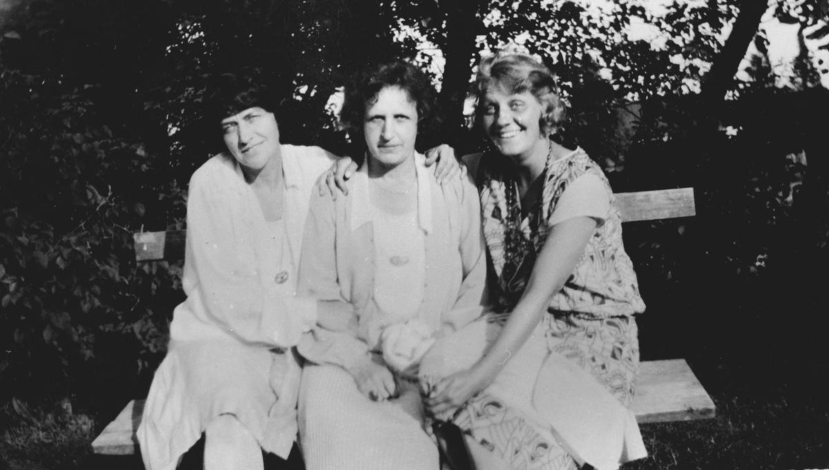 3 kvinner på en benk i hagen