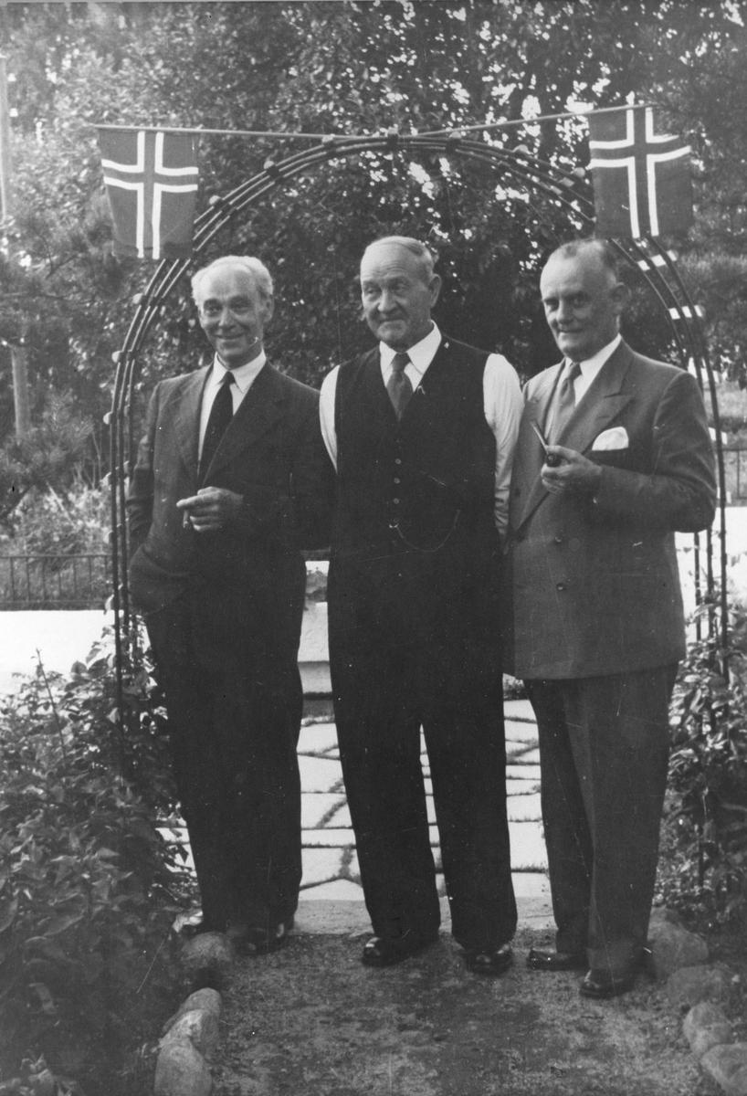 Harald Stubberuds 80-årsdag. Tre menn i en flaggprydet portal.