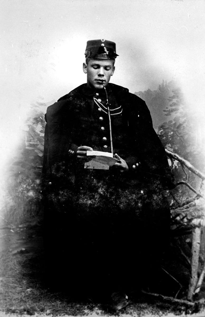 Soldat som røker langpipe og leser et brev.