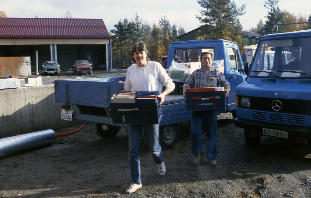 Rune og Per Chrisian bærer inn kasser.