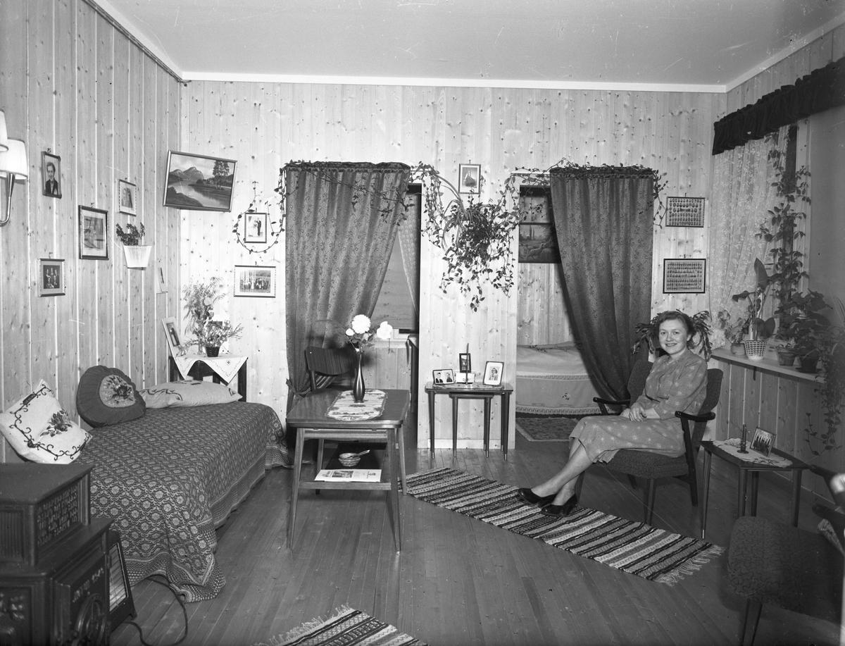 Bjerkely. Kvinne i stue med 2 sovealkover.