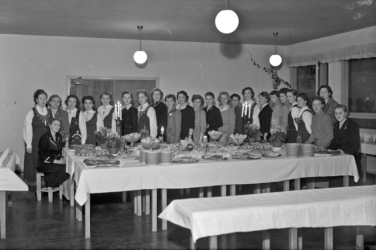Gruppe jenter ved et bord med kaker.