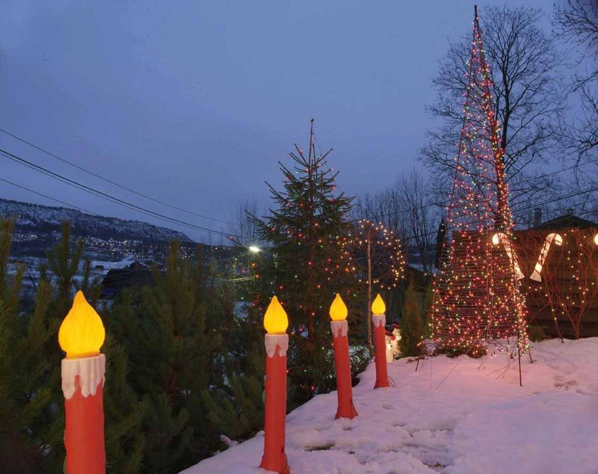 Julebelysning  Fantastisk julebelysning på enebolig. Lysende  stearinlys, sukkertøy og flerfarget pyramide i hage.