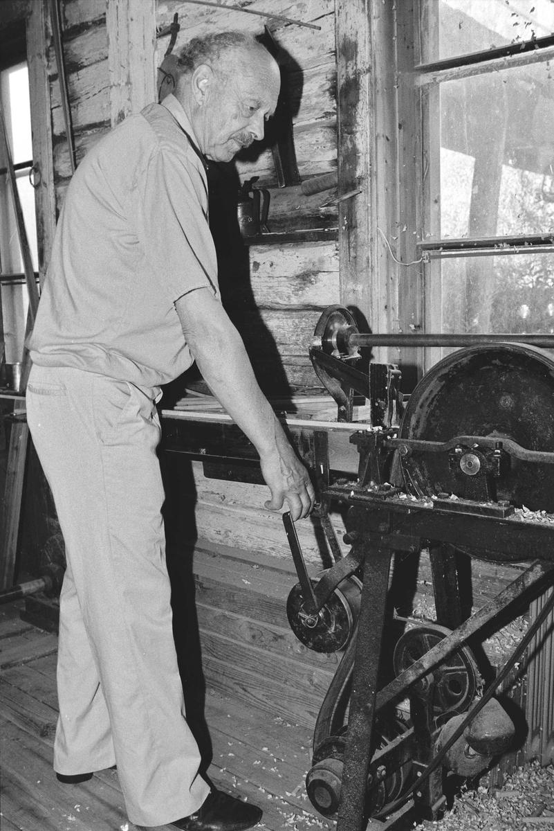 Svartdahl Bruk Bærepinneproduksjon. Demonstrasjon av maskiner. Innkobling av drivreim på pinnemaskin. Det tunge hjulet til venstre strammer reima, slik at den griper tak i reimskivene til dreie og fremtrekksapparatene og kobler dem til drivakselen. Per Iversen demonstrerer.