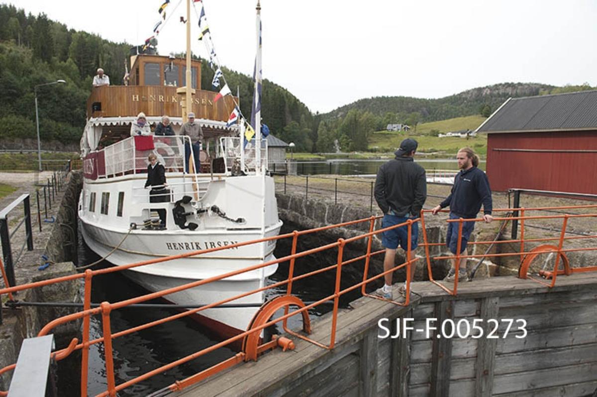 Turistbåten «Henrik Ibsen» i Kjeldal sluse i Bandak-Norsjø-kanalen.  Sluseanlegget ligger i Nome kommune.  Her er det ett slusekammer, som utlikner en høydeforskjell på tre meter mellom ovenforliggende og nedenforliggende del av vassdraget.  Sluseanleggene betjenes i 2012 av to slusevoktere som reiser foran rutebåtene i bil.  Her ser vi karene på brua over nedre sluseport. Båten går i rute mellom Skien by og Dalen i Tokke, innerst ved Bandakvatnet, en distanse på 105 kilometer.  Henrik Ibsen er det største, raskeste og mest luksuriøse skipet i Skiensvassdraget.  Fartøyet er opprinnelig bygd som dampskip ved Eriksbergs Mekaniska Verkstad i Gøteborg i 1907 for Styrsö-bolaget.  Derfor fikk båten først navnet DS «Styrsö».  Under dette navnet gikk fartøyet i mange år som rutebåt i Gøteborg-skjærgården.  Etter en periode som charterbåt på den svenske vestkysten ble Styrsö oppkjøpt av Skien Dalen Skipsselskap AS og satt trafikk i Skiensvassdraget i forbindelse med Bandak-Norsjø-kanalens 100-årsjubileum i 1992.  Her fikk båten navnet «MS Henrik Ibsen», etter den berømte forfatteren med tilknytning til Skien og en hurtiggående dampbåt som gikk i vassdraget tidig på 1900-tallet.  I perioden 2009-2011 ble skipet restaurert med sikte på at det igjen skulle framstå som det hadde gjort da det var nytt.  Etter dette har fartøyet vært driftet av Norwegian Hospitality Group AS, som eier Telemarkskanalen Skipsselskap AS.  Selskapet disponerer også det tradisjonsrike drakestilhotellet på Dalen, som er endestasjon for båtruta.  Sesongen for kanalbåtene starter vanligvis i midten av mai og varte til andre halvdel av september. Seilasen mellom Skien og Dalen med turistbåten Henrik Ibsen tar cirka ni timer. MS Henrik Ibsen har aller rettigheter og det er restaurant ombord med daglig servering av frokost og lunsjretter.  Båten går opp den ene dagen og ned igjen den neste.  Turistbåten MS Victoria går ned til Skien den dagen Henrik Ibsen setter kurs for Dalen, og går ned igjen den dagen den